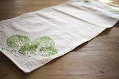 Caminos de mesa o manteles pintados a mano con pintura para tela y hojas de árboles y arbustos.