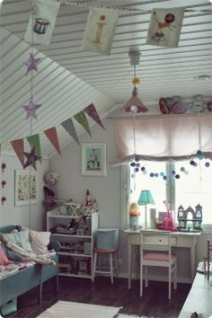 Fun girls bedroom with various banners hanging in different directions by V a l k e a a U n e l m a a