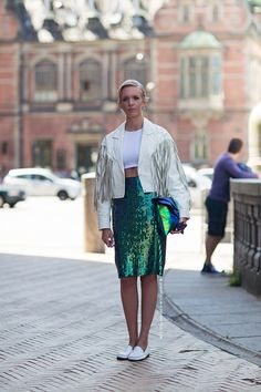 Caroline in a white fringe leather jacket, iridescent sequin pencil skirt, cropped top, and white loafers.