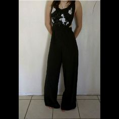 Sexy Black Jumpsuit This jumpsuit is in Absolute Perfect condition, except the tag is ripped in two . The straps are adjustable , the front design has silver flowers with a light pink middle, the material is so smooth, and the sides and back are open as shown in pics 2&3 it has black sequins on the top design and is just absolutely Lovely. Beautiful, but deep neckline, I'm 5'6 and it kind of rides up. Take Reasonable offers. Mustard Seed Dresses Backless