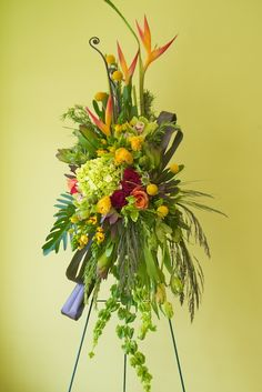 Red and orange roses, yellow pompons, bird of paradise, gladioli.
