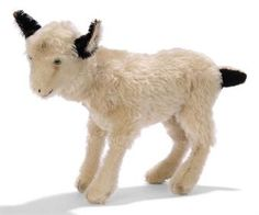 A STEIFF HEAD-TURNING GOAT, (1329,0 H), standing, pale brown mohair, green and black glass eyes, black stitching, black mohair ears and tail, tail-operated head-turning mechanism, inoperative squeaker and FF button with remains of red cloth tag, circa 1933 --10½in. (27cm.) high (some slight wear and fading)