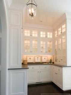 Fabulous u-shaped butlers pantry with ceiling height white cabinetry and granite countertops.