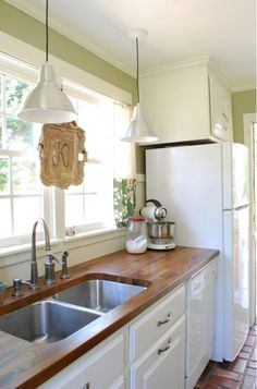 Kitchen Design Ideas - Butcher block counter top and recessed sink. Also the white appliances and lighting.