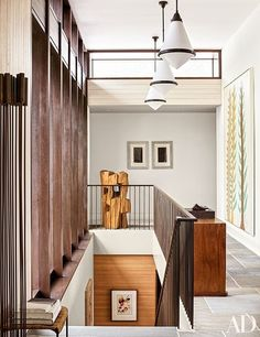 A minimalist staircase is surrounded by art in a Hamptons home reimagined by architect Deborah Berke and designer Thomas O'Brien.