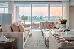Decoração de casa ampla e confortável com ambientes integrados e pronta para receber, na sala uma lareira, decoração em tons neutros, plantas na decoração e paredes de vidro.