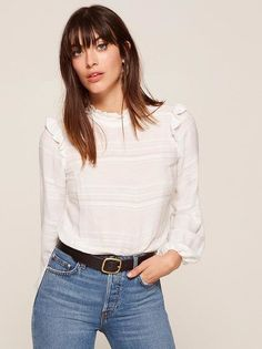 Let the ruffles do the talking. This is a relaxed fitting top with a high, ruffled neck and ruffled shoulders.