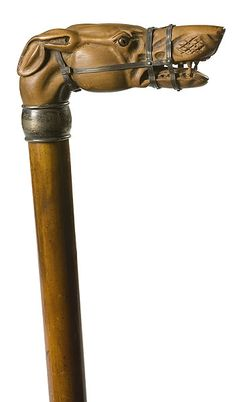 "TIFFANY AND CO. CANE WITH MUZZLED GREYHOUND HANDLE. American, ca 1900. The greyhound's head in carved wood, with glass eyes; the collar marked Tiffany and Co/Makers/Sterling, and engraved Wm.G.A. Turner 1900; 35"" long."