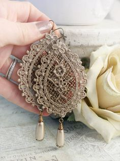 ______________________________________________________________________________    Lace and pearls go together like chocolate and peanut butter...  ______________________________________________________________________________    These intricate, eye-catching earrings celebrate all things Victorian with an antique twist. They are approx. 3.75 long and feature splendid tear drop venice lace focals, dyed to a shimmering antique bronze tone. Each lace focal leads down to a taupe pearl drop with…