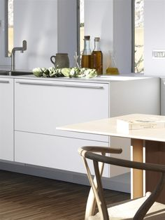bulthaup c3 table with Wishbone Chair in a  home near Barcelona, Spain. The b3 wall-hung kitchen in the background is finished in Alpine white. www.bulthaup.com #bulthaup #kitchens #modernkitchens