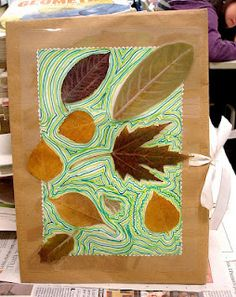 a folder to collect herbs, with cardboard, wrapping paper, leaves, paper, crayons and colored ribbons.