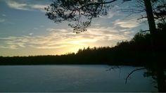 Sun setting on a pond in a Finnish forest. Auringonlasku metsälammella.