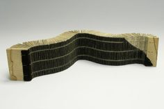 """Susan Porteous - Eclipse, recycled book, linen thread, leather, wood, 16 1/2"""" x 3 1/2"""" x 2 1/4""""; An experimental book in which the pages get progressively wider along its length. It is bound onto a strip of leather that covers all but one corner of the spine and front cover."""