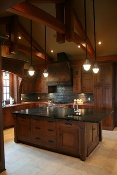 Dark wood and island lighting. Would want butcher block counter and perpendicular T shaped black bar stool area/ serving counter.