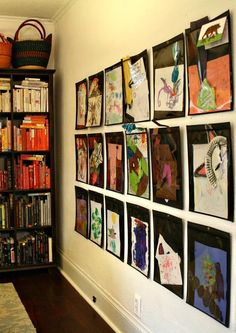 """The couple created a gallery wall to hold an ever-changing display of the kids' artwork. ~but where can I buy the """"plastic envelope sheaths""""?"""