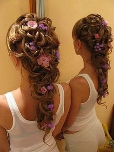 Cascades of curls with intermingled flowers make a sophisticated look for any wedding or formal event.