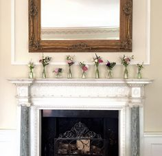 A mantelpiece of delicate, country flowers for a March wedding at Goldsborough Hall. Flowers by Lucy MacNicholl