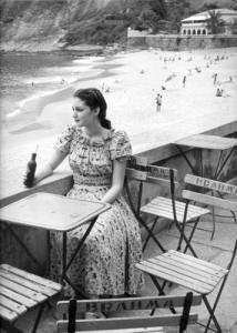 177 PRAIA VERMELHA – URCA – DÉCADA DE 1950  Nesta foto de J. Medeiros, da década de 1950, vemos uma moça tomando um Crush, na Praia Vermelha, na Urca.  O tom avermelhado das areias conferindo um diferencial em relação às outras praias do Rio batizou este recanto como Praia Vermelha.