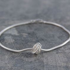Our signature piece, this hand-woven sterling silver nest charm is attached to a thick snake chain bracelet. Perfect for everyday wear or special occasions. #Otisjaxon #Jewellery #Accessories #Bracelet #Bangle #Women