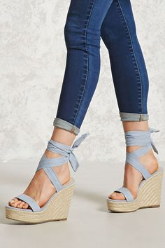 A pair of faux suede espadrilles with a braided wedge heel, a self-tying ankle wrap, and an open toe.