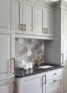Gray kitchen pantry cabinets accented with brushed brass hardware flanks gray raised panel cabinets topped with a honed black marble countertop fitted with a sink and an antique brass vintage style faucet mounted in front of black and white hex mosaic backsplash tiles beneath gray upper cabinets.