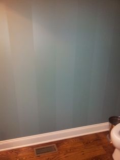 Vertical stripes achieved by using the same paint color in two different sheen levels, matte and satin.  A nice way to add some interest to a small powder room.