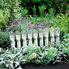 """concrete """"helping hands"""" for the garden.  Loks like they have just filled concrete into rubber gloves & probably painted the finished product white."""