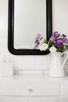 Simple white bathroom with black mirror.