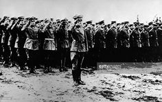 German flying ace Baron Manfred von Richthofen (1892 - 1918) salutes in front of the officers and staff of Fighting Squadron No. 11 as they stand in formation, 191Os. Von Richthofen, known as the Red Baron, is considered the most successful fighter pilot of all time, racking up 80 air combat battles in less than two years.