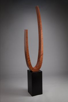 Free Standing Sculpture by Richard Judd. High figure pommele sapele veneer over a vacuum formed birch bent ply lamination arcing form set on a solid poplar base finished in black varnish. The negative space of the arc is an elliptical form. This is an abstract form without a figurative representation. Inspiration comes from the work of Brancusi. This sculpture celebrates the beauty of the wood.