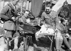 Tank officers relaxing around a gramophone player with their pet dog, in camp at Poperinghe, 26 September 1917.