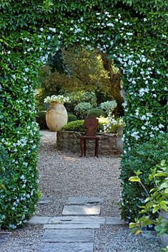 DESIGNER MICHEL SEMINI PROVENCE FRANCE. VIEW THROUGH DOORWAY WITH TRACHELOSPERMUM JASMINOIDES TO GRAVEL COURTYARD WITH TERRACOTTA CONTAINER AND ORNATE METAL SEATS