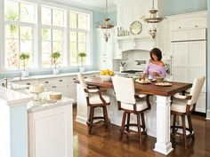 white kitchen with blue walls with large uncovered windows