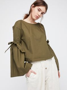 So Obvious Solid Top | Ultimate cool girl top with a structured feel. Features dramatic flared sleeves and a skin baring open back with adjustable ties at both details.