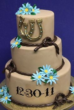 Western-themed wedding cake with rope design and gold horse shoes #wedding…