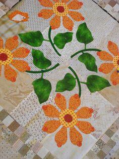 Appliquéd flowers on a pieced background.