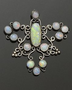 An Arts and Crafts opal pendant  Of scrolling openwork design, collet set with oval and circular cabochon opals, white precious metal mounted, unmarked, length 5cm.