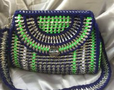 Purse made with pop tabs using neon green nylon yarn. Sewn in silver silky fabric liner. Small size purse for day-to-day use.Can be used with short strap, long strap and or handheld. Has a magnetic closure. Also has 3 butterfly beads on front flap. Show your love of recycling. Pop tabs are a recycled material and used for the purse and the strap. Purse is 8 inches x 6 inches x 2 inches. Removable strap, strap drop is 18.5 inches from shoulder. Has Lucky Fairy Penny Purse attached to Label…