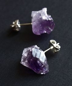 "Handmade raw amethyst chunk stud earrings. Approx. 1/2"" long chunks of raw, naturally variegated amethyst. Silver metal posts with backs. Lightweight and low key, but still funky. Stones will vary naturally from earring to earring. Several different pairs of earrings are seen in the pictures; you will receive one of the pairs. Amethyst; silver metal posts and backs By Adam Rabbit. Handmade in Arizona"