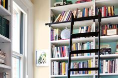 A handsome and useful rolling ladder works well in a kitchen, to reach high cabinets; in a family room with a towering bookcase; or even in a cheerful reading nook, like this one! See our DIY instructions | Photo: Bruce Buck