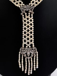 Art Deco natural pearl and diamond necklace Neck width: 54 cm. Length of the central part: approx. 11.6 cm Total weight: approximately 35.1 g. Platinum. Probably France, circa 1920. elaborately knotted Art Deco necklace with small, slightly cream-colored Oriental pearls with subtle luster, diameter from about 2.1 to about 3.3 mm, and cushion and rose-cut diamonds, altogether approx 2:20 CT. One closure link broken, missing Both small pearls are enclosed.