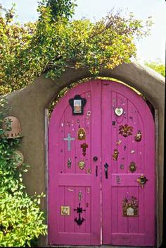 Pink doorway decorated with milagros, Santa Fe, New Mexico, ca. 1973-2010. Photo by Jack Parsons. Palace of the Governors Photo Archives HP.2007.11.39.