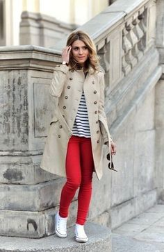 Una gabardina beige y unos vaqueros pitillo rojos son prendas que debes tener en tu armario. Zapatillas altas de lona blancas contrastarán muy bien con el resto del conjunto.