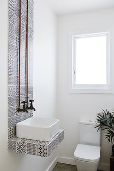 Interesting details (the continuous splash back and exposed pipes) to a toilet and sink small space. There's no mirror for your guests though.