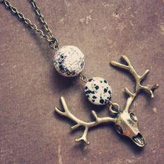 a long beaded deer skull necklace.