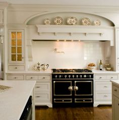 A black French range is the latest focal point In two all-white kitchens with bright white cabinets, light counters and vent hoods that showcase the range.