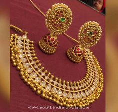 traditional gold necklace studded with white stones and embellished with clustered golden balls. The necklace set has matching jhumka earrings studded with kemp rubies and emeralds. Gold Earrings Designs, Gold Jewellery Design, Necklace Designs, Gold Jewelry, Diamond Jewellery, Statement Jewelry, India Jewelry, Temple Jewellery, Antique Necklace