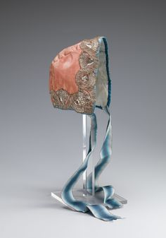 Child's cap, Norway, second half 18th century. Pink silk taffeta, silver metall lace decoration, cream silk lining, blue striped silk ribbon binding.