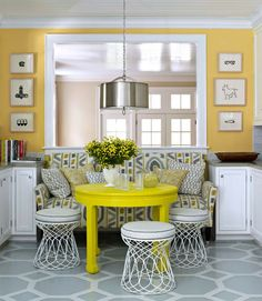 In this cozy dining space, a bright yellow table is surrounded by unexpected seating --an upholstered settee and round wire stools. I love the silver shade on that chain-hung pendant light.