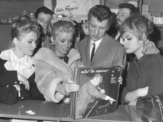 Johnny Hallyday and actress Catherine Deneuve find a copy of Hallyday's Salut les Copains album at a record shop in Paris in 1962.